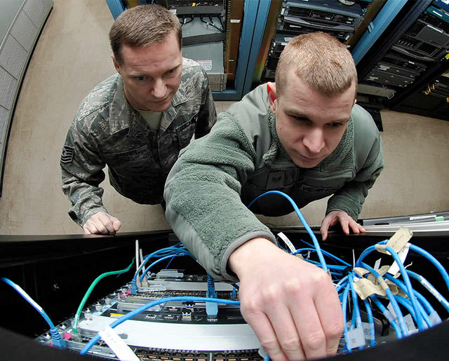 Airmen hooking up router cables